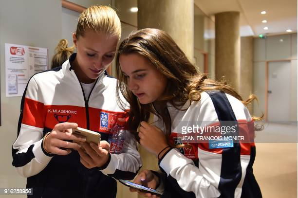 France's Kristina Mladenovic and France's Clara Burel check their smartphone following the draw of the Fed Cup World Group first round tennis match...