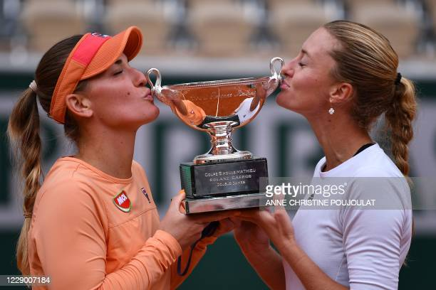France's Kristina Mladenovic and Hungary's Timea Babos kiss the Simonne Mathieu Cup after winning against Chile's Alexa Guarachi and Desirae Krawczyk...
