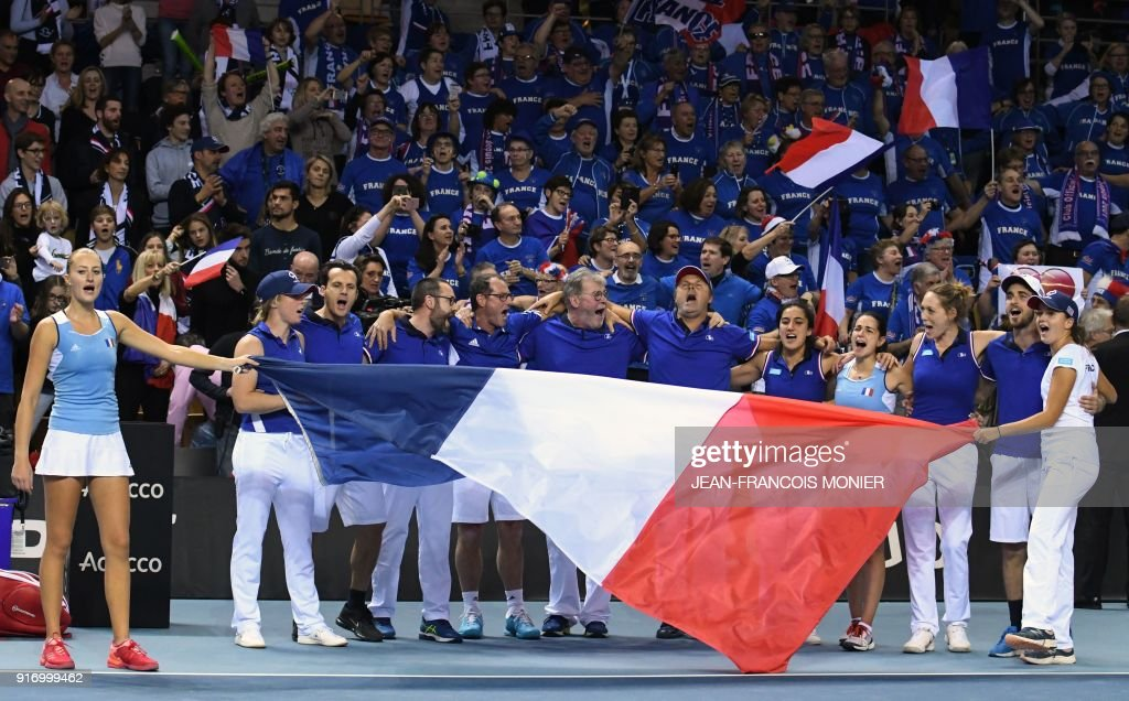 France's Kristina Mladenovic (L) celebrates with France's team after winning with her teammate Amandine Hesse against Belgium's Kirsten Flipkens and Elise Mertens during the Fed Cup World Group first round double tennis match between France and Belgium in Mouilleron-le-Captif, northwestern France, on February 11, 2018. France made the semi-finals for the third time in four years when Kristina Mladenovic won her third point of the weekend by teaming with world number 228 Amandine Hesse to beat Kirsten Flipkens and Elise Mertens 6-4, 2-6, 6-2 in the deciding doubles. / AFP PHOTO / Jean-Francois MONIER