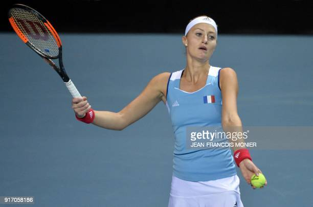 France's Kristina Mladenovic serves the ball during the double tennis match with teammate France's Amandine Hesse against Belgium's Elise Mertens and...