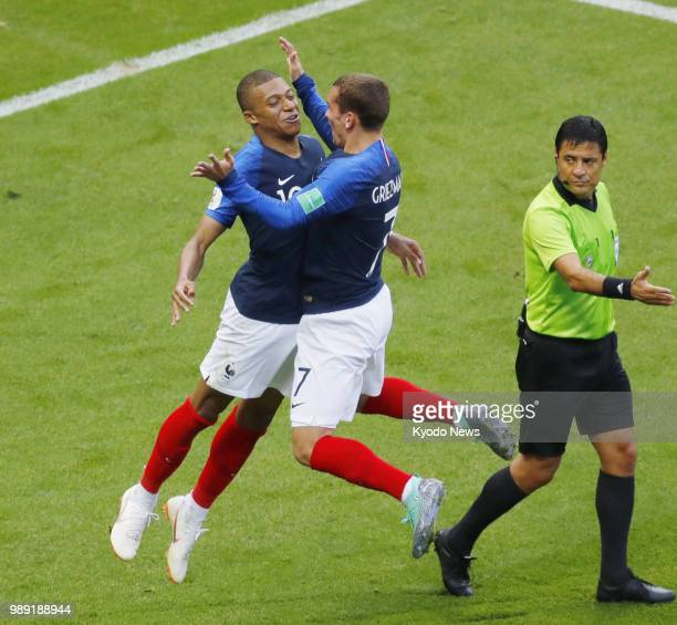 France's Kylian Mbappe celebrates with his teammate Antoine Griezmann after scoring the third goal for his side during the second half of a World Cup...