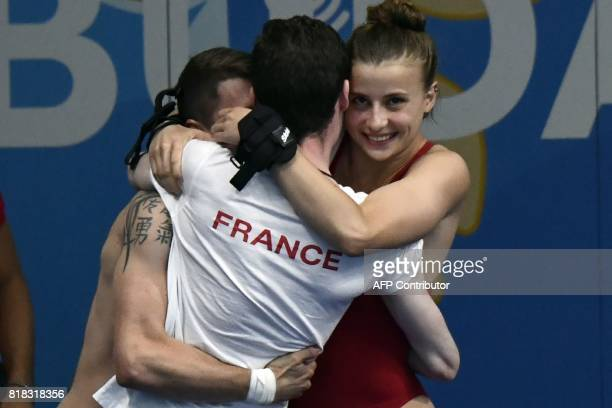 France's Laura Marino and France's Matthieu Rosset react with their team after winning the 3m/10m team event during the diving competition at the...