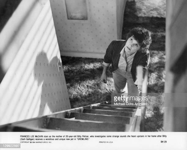 Frances Lee McCain looking up a ladder in a scene from the film 'Gremlins' 1984