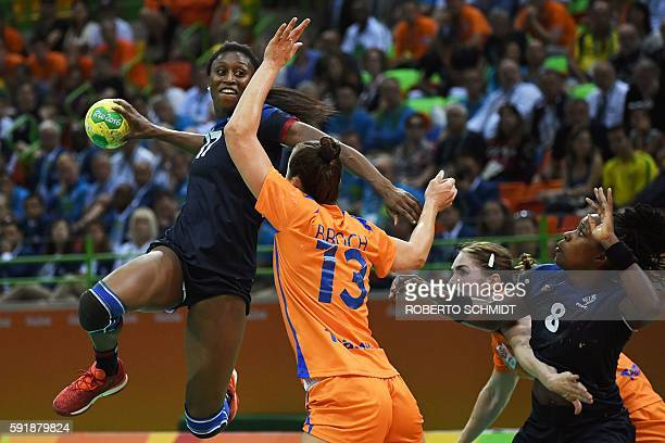 TOPSHOT France's left wing Siraba Dembele shoots past Netherlands' pivot Yvette Broch and France's pivot Laurisa Landre during the women's semifinal...