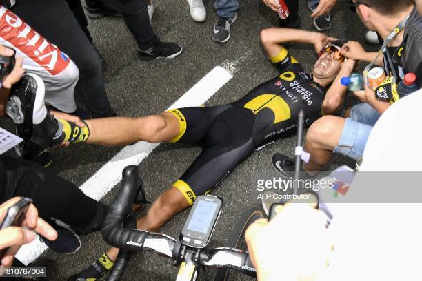 TOPSHOT France's Lilian Calmejane suffering from cramps receives assistance after he crossed the finish line at the end of the 1875 km eighth stage...