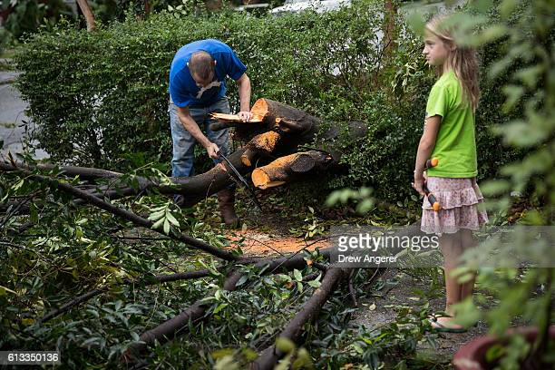 Frances Long looks on as her father Rudd Long saws branches from a downed elm tree that fell in front of his home October 8 2016 in Savannah Georgia...