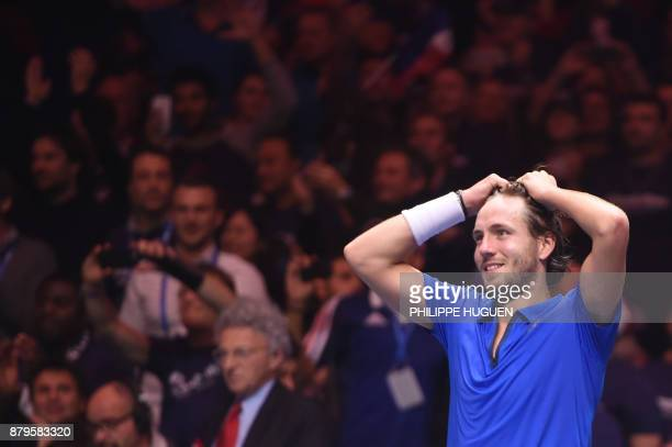 France's Lucas Pouille celebrates after winning his singles rubber 5 match against Belgium's Steve Darcis at the Davis Cup World Group final tennis...