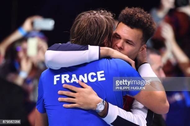 France's Lucas Pouille celebrates with France's JoWilfried Tsonga after winning his singles rubber 5 match against Belgium's Steve Darcis at the...