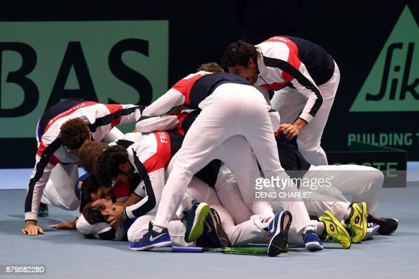 France's Lucas Pouille celebrates with his teammates after winning his singles rubber 5 match against Belgium's Steve Darcis at the Davis Cup World...