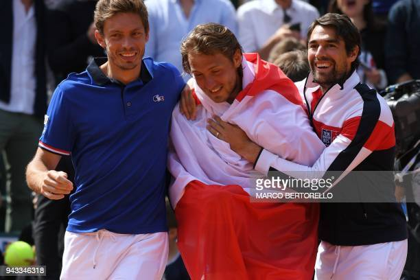 France's Lucas Pouille celebrates with teammates Jeremy Chardy and Nicolas Mahut after winning the Davis Cup quarter final Italy vs France against...
