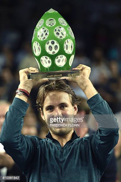France's Lucas Pouille holdsup the trophy after defeating Austria's Dominic Thiem during the ATP Moselle Open finals tennis match on September 25...