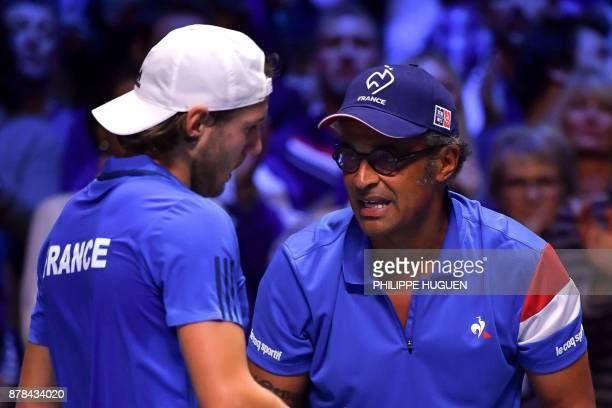 France's Lucas Pouille reacts next to captain Yannick Noah after losing a point to Belgium's David Goffin during their Davis Cup World Group singles...