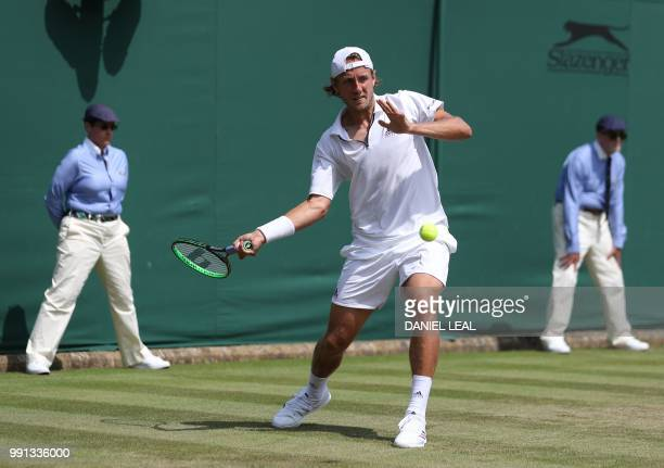 France's Lucas Pouille returns to Austria's Dennis Novak during their men's singles second round match on the third day of the 2018 Wimbledon...