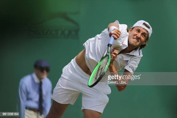 France's Lucas Pouille serves to Austria's Dennis Novak during their men's singles second round match on the third day of the 2018 Wimbledon...