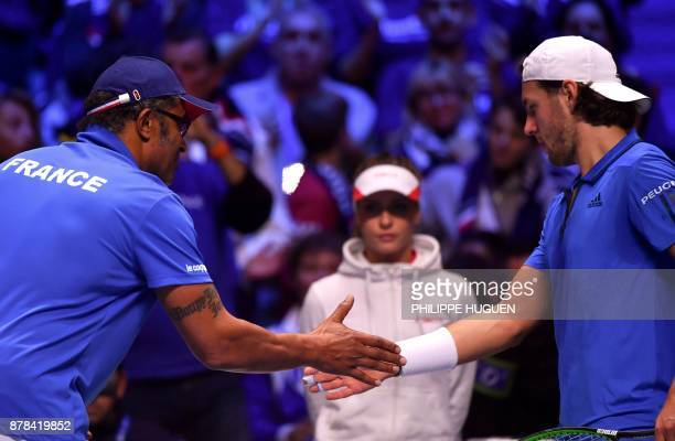 France's Lucas Pouille shakes hands with captain Yannick Noah after winning a point during the Davis Cup World Group singles rubber final tennis...