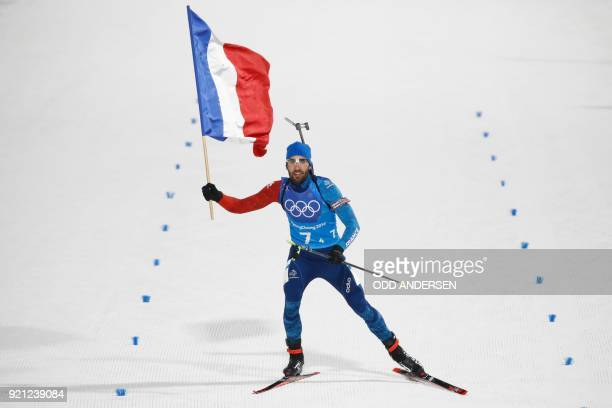 TOPSHOT France's Martin Fourcade celebrate team gold after crossing the finish line in the mixed relay biathlon event during the Pyeongchang 2018...