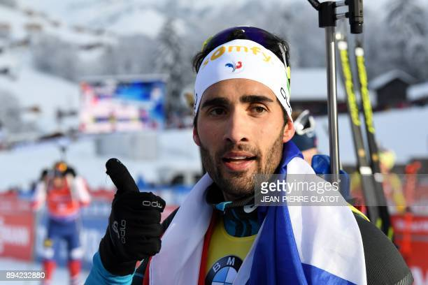 France's Martin Fourcade celebrates after winning the 15 km men's Mass Start during the IBU World Cup Biathlon 3 in Le Grand Bornand on December 17...