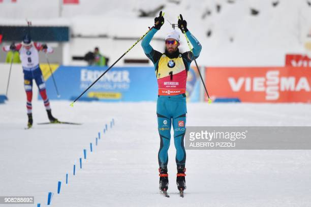 France's Martin Fourcade celebrates as he crosses the finish line to win the Men 15 km Mass Start Competition of the IBU World Cup Biathlon in...