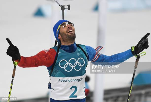 TOPSHOT France's Martin Fourcade celebrates winning gold at the finish line in the men's 15km mass start biathlon event during the Pyeongchang 2018...