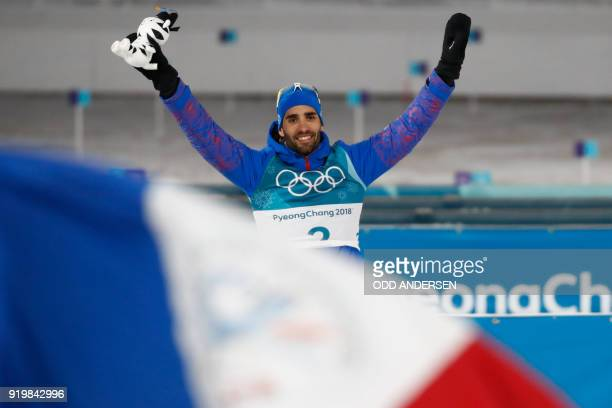 TOPSHOT France's Martin Fourcade celebrates winning gold during the victory ceremony in the men's 15km mass start biathlon event during the...