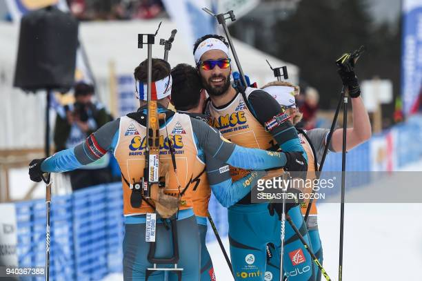 France's Martin Fourcade celebrates with teammates after competing in the mass start Premanon French Biathlon Championships on March 31 2018 in...