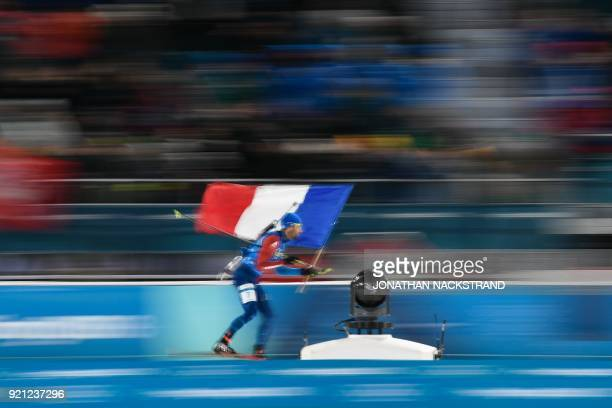 TOPSHOT France's Martin Fourcade cross the finish line to win team gold in the mixed relay biathlon event during the Pyeongchang 2018 Winter Olympic...