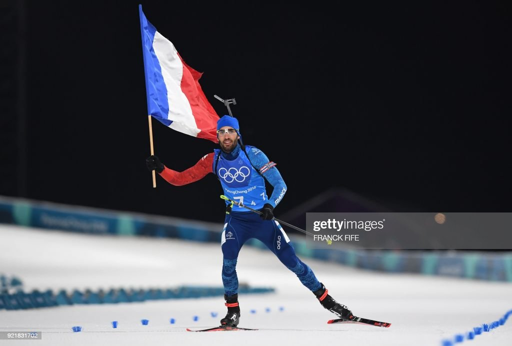 TOPSHOT - France's Martin Fourcade crosses the finish line to win team gold in the mixed relay biathlon event during the Pyeongchang 2018 Winter Olympic Games on February 20, 2018, in Pyeongchang. /