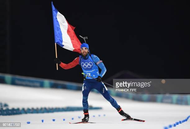 TOPSHOT France's Martin Fourcade crosses the finish line to win team gold in the mixed relay biathlon event during the Pyeongchang 2018 Winter...