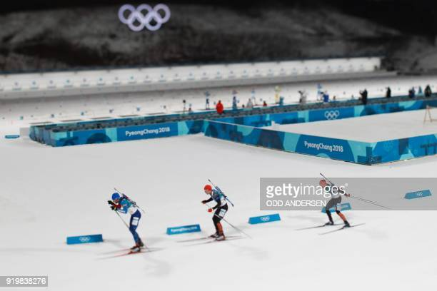 TOPSHOT France's Martin Fourcade Germany's Simon Schempp and Germany's Erik Lesser compete in the men's 15km mass start biathlon event during the...