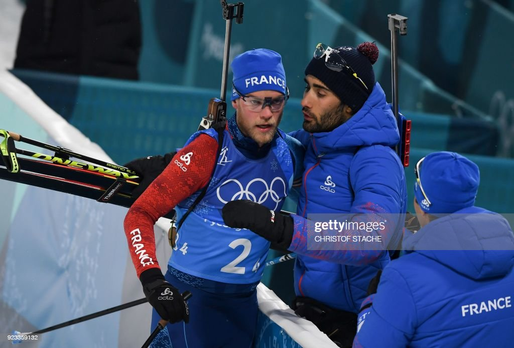 TOPSHOT - France's Martin Fourcade (C) greets France's Antonin Guigonnat as he crosses the finish line in the men's 4x7,5km biathlon relay event during the Pyeongchang 2018 Winter Olympic Games on February 23, 2018, in Pyeongchang. / AFP PHOTO / Christof STACHE