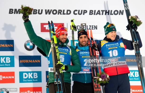 France's Martin Fourcade jumps as he celebrates his victory on the podium next to the second placed Germany's Arnd Peiffer and third placed Vetle...