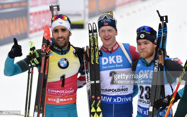 France's Martin Fourcade, Norway's Johannes Thingnes Boe and France's Antonin Guigonnat pose after the men's 15 kilometer mass start competition at...