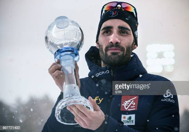 France's Martin Fourcade poses with the crystal globe trophy following the mass start event at the IBU Biathlon World Cup Final in Tyumen on March 25...