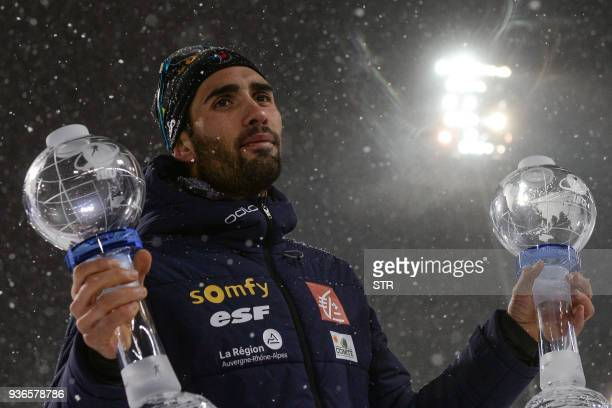 TOPSHOT France's Martin Fourcade poses with the small sprint crystal globe and the small globe for the individuals after winning the men's 10 km...
