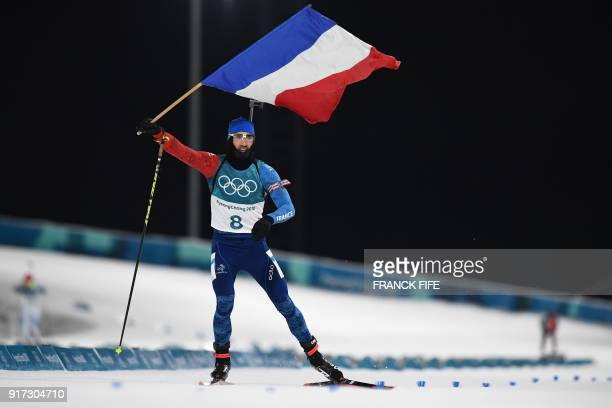 TOPSHOT France's Martin Fourcade waves the French flag as he wins the men's 125km pursuit biathlon event during the Pyeongchang 2018 Winter Olympic...