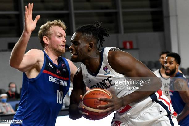 France's Mathias Lessort fights for the ball with Britain's Dan Clark during the FIBA EuroBasket 2022 qualifier basketball match between France and...