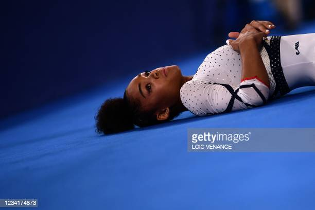 France's Melanie De Jesus Dos Santos rests during the women's qualification during the Tokyo 2020 Olympic Games at the Ariake Gymnastics Centre in...