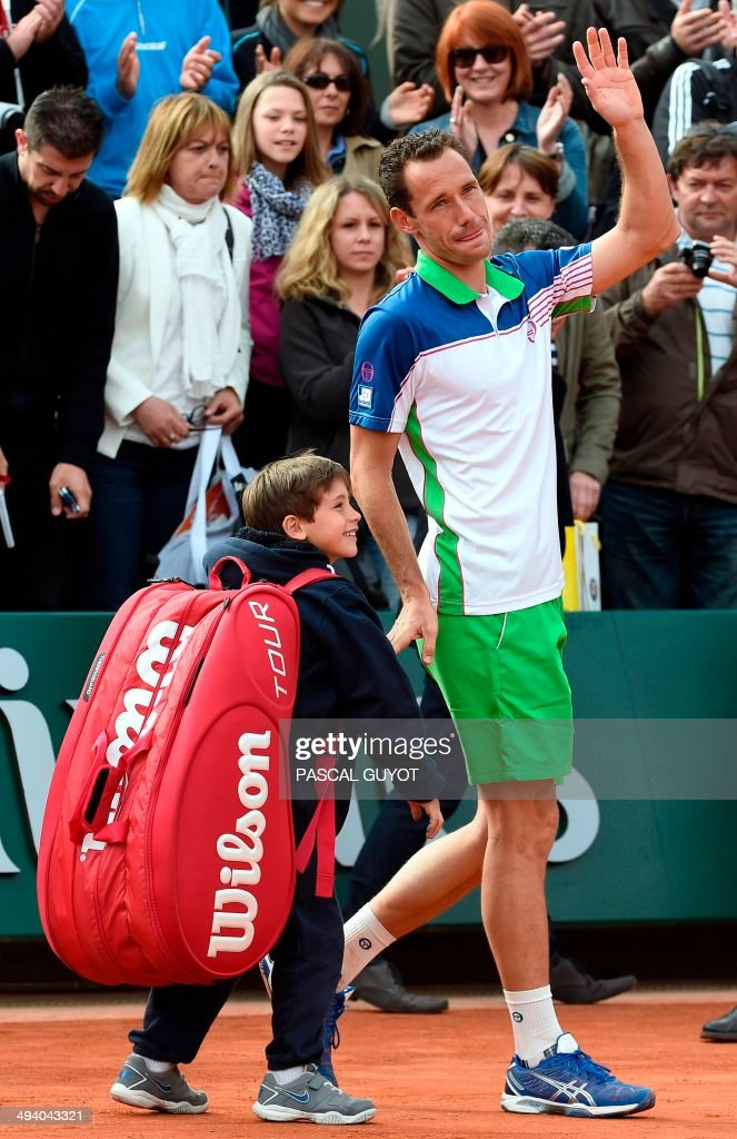 France's Michael Llodra acknowledges the audience next to his son during a ceremony held on the occasion of his last professionnal match at the French tennis Open at the end of his first round match at the Roland Garros stadium in Paris on May 27, 2014.