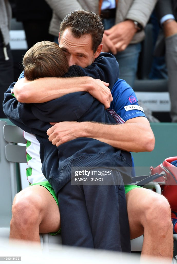 France's Michael Llodra embraces his son during a ceremony held on the occasion of his last professionnal match at the French tennis Open at the end of his first round match at the Roland Garros stadium in Paris on May 27, 2014.