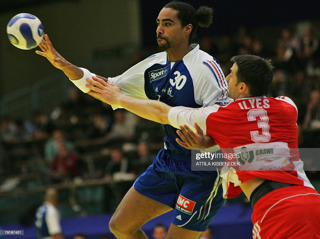 France's middle back Fabrice Guilbert (L) passes the ball as he vies with Hungary's left back Ferenc Ilyes during their 8th Men's European Handball Championship Main Round match, 24 January 2008 at the Spektrum sports hall in Trondheim.