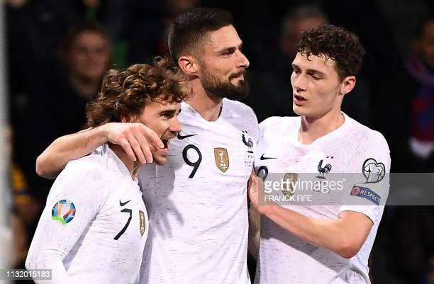 France's midfielder Antoine Griezmann is congratulated by France's forward Olivier Giroud and France's defender Benjamin Pavard after scoring a goal...