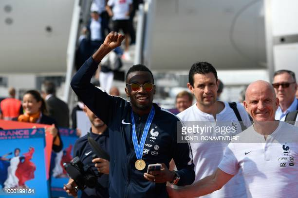 France's midfielder Blaise Matuidi flanked by France's assistant coach Guy Stephan waves to fans after disembarking from the plane with teammates...