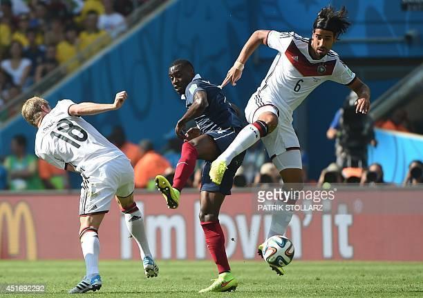 France's midfielder Blaise Matuidi tackles Germany's midfielder Sami Khedira and Germany's midfielder Toni Kroos during the quarterfinal football...