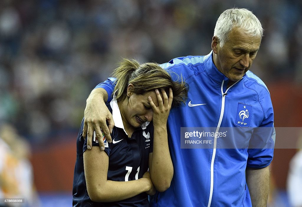 France's midfielder Claire Lavogez (L) is helped by France's head coach Philippe Bergeroo during the quarter-final football match between Germany and France in the 2015 FIFA Women's World Cup at the Olympic Stadium in Montreal on June 26, 2015.