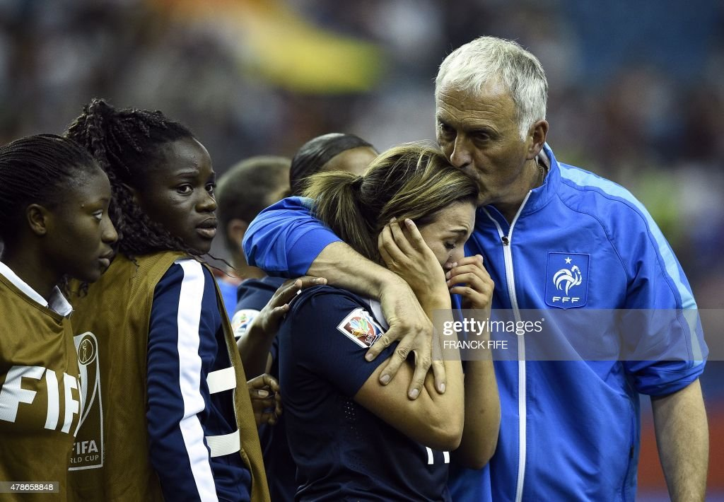 France's midfielder Claire Lavogez (C) is helped by France's head coach Philippe Bergeroo after missing a goal during the quarter-final football match between Germany and France in the 2015 FIFA Women's World Cup at the Olympic Stadium in Montreal on June 26, 2015.