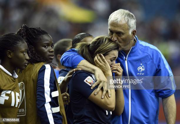 France's midfielder Claire Lavogez is helped by France's head coach Philippe Bergeroo after missing a goal during the quarter-final football match...