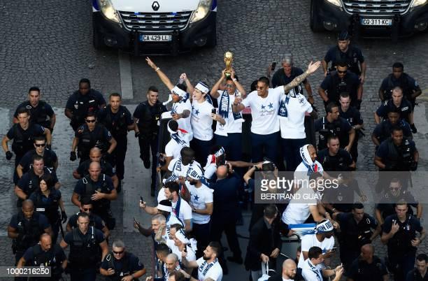France's midfielder Corentin Tolisso France's defender Benjamin Pavard France's defender Raphael Varane holding the trophy and France's goalkeeper...