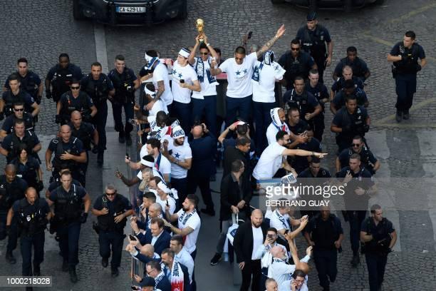 France's midfielder Corentin Tolisso France's defender Benjamin Pavard France's defender Raphael Varane holding the trophy France's goalkeeper...