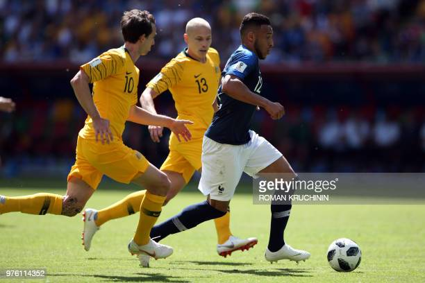 France's midfielder Corentin Tolisso is chased by Australia's forward Robbie Kruse and Australia's midfielder Aaron Mooy during the Russia 2018 World...