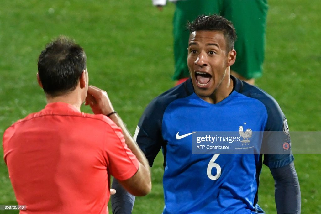 France's midfielder Corentin Tolisso (R) speaks with referee Antonio Mateu Lahoz during the FIFA World Cup 2018 qualifying football match between Bulgaria and France at The Vasil Levski Stadium in Sofia on October 7, 2017. / AFP PHOTO / Nikolay DOYCHINOV
